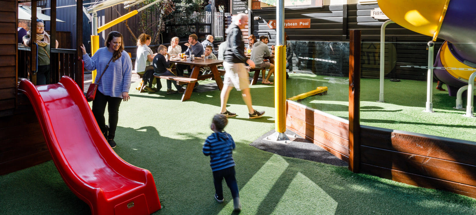 Families dining in kids play area at cafe